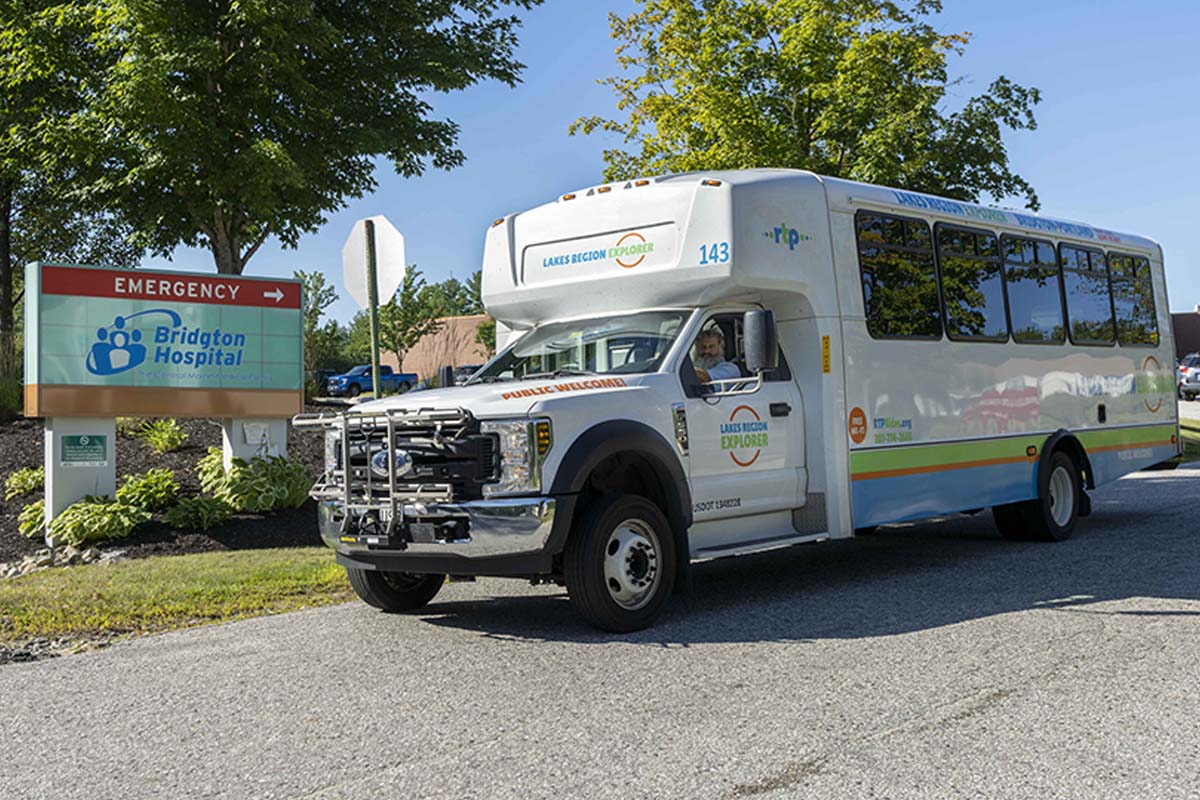 Driver, Bob G in Lake Region Explorere bus at Bridgton Hospital sign